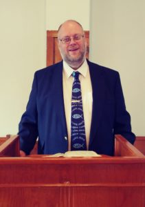 Picture of Pastor Jonathan Elliott behind the pulpit.